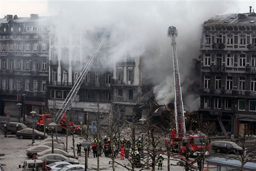 Firemen try to extinguish a fire in a collapsed building in Liege, Belgium, Wednesday, Jan. 27, 2010. (AP Photo/Geert Vanden Wijngaert)