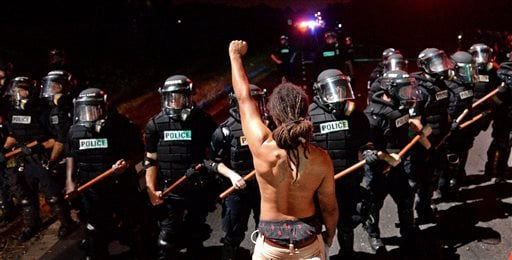A protester stands with his left arm extended and fist clenched in front of a line of police officers in Charlotte, N.C. on Tuesday, Sept. 20, 2016. Authorities used tear gas to disperse protesters in an overnight demonstration that broke out Tuesday afte
