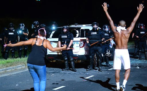 Protesters approach police in Charlotte, N.C., Tuesday, Sept. 20, 2016. Authorities used tear gas to disperse protesters in an overnight demonstration that broke out Tuesday after Keith Lamont Scott was fatally shot by an officer at an apartment complex.