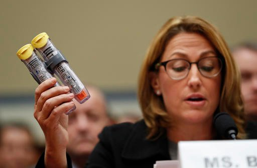Mylan CEO Heather Bresch holds up an EpiPen while testifying on Capitol Hill in Washington, Wednesday, Sept. 21, 2016, before the House Oversight Committee hearing on EpiPen price increases. Bresch defended the cost for life-saving EpiPens, signaling the
