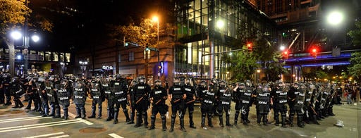 CMPD officers in riot gear block the intersection near the Epicentre in Charlotte, N.C.