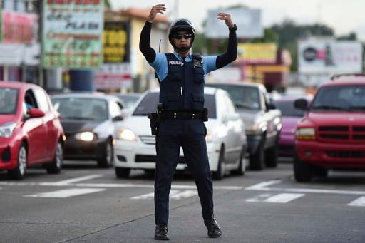 A transit police officer directs the flow of traffic at an intersection in San Juan.