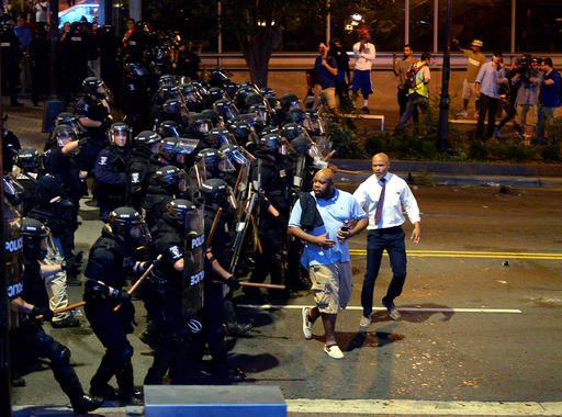Charlotte-Mecklenburg police officers begin to push protesters from the intersection near the Epicentre in Charlotte, N.C.