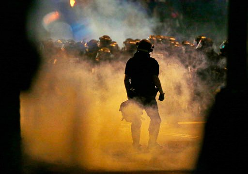 Police fire teargas as protestors converge on downtown following Tuesday's police shooting of Keith Lamont Scott in Charlotte, N.C.