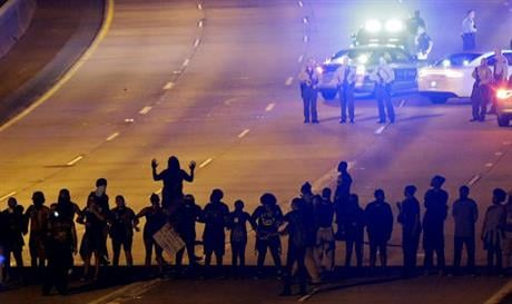 Protesters block I-277 during a third night of unrest following Tuesday's police shooting of Keith Lamont Scott in Charlotte, N.C., Thursday, Sept. 22, 2016. (AP Photo/Gerry Broome)