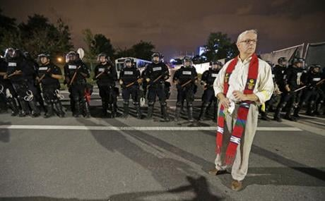 A member of the clergy stands in front of a line of police officers in Charlotte, N.C. Thursday, Sept. 22, 2016. blocking the access road to I-277 on the third night of protests following Tuesday's fatal police shooting of Keith Lamont Scott. (AP Photo/Ch