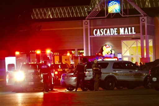 Law enforcement officers work at the crime scene outside of Cascade Mall in Burlington, Wash.