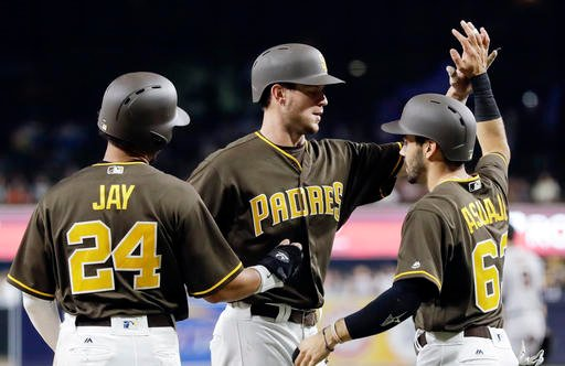 The San Diego Padres' Wil Myers, center, reacts with teammates Jon Jay, left, and Carlos Asuaje, right, after hitting a three-run home run.