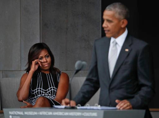First lady Michelle Obama wipes her eyes as she listens to her husband, President Barack Obama, speak.