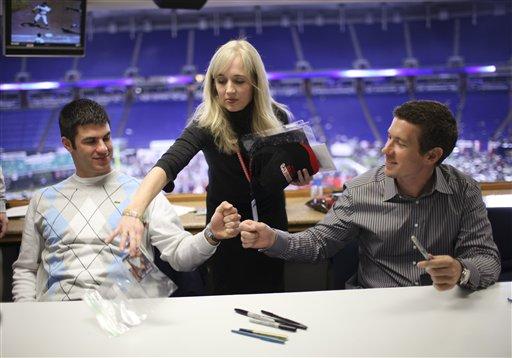 Twins front office staffer Nancy O'Brien, center, retrieves the last item signed by Mauer for a fan. (AP Photo/Star Tribune, Jeff Wheeler)