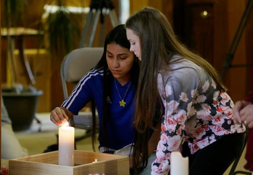 Rachel Marsh, 15, right, and Selena Orozco, 15, left, light candles as they attend a prayer service, Saturday, Sept. 24, 2016, at the Central United Methodist Church in Sedro-Woolley, Wash. The service was held in reaction to Friday's fatal shooting of se