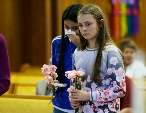Rachel Marsh, 15, right, and Selena Orozco, 15, left, carry flowers as they attend a prayer service, Saturday, Sept. 24, 2016, at the Central United Methodist Church in Sedro-Woolley, Wash. The service was held in regard to Friday's fatal shooting of seve