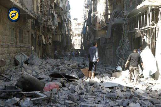 In this photo provided by the Syrian Civil Defense group known as the White Helmets, shows Syrian inspect damaged buildings after airstrikes hit in Aleppo, Syria, Saturday, Sept. 24, 2016. Syrian government forces captured a rebel-held area on the edge of