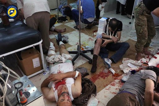 In this photo provided by the Syrian Civil Defense group known as the White Helmets, shows wounded men receiving treatment at a local clinic after airstrikes hit in Aleppo, Syria, Saturday, Sept. 24, 2016. Syrian government forces captured a rebel-held ar
