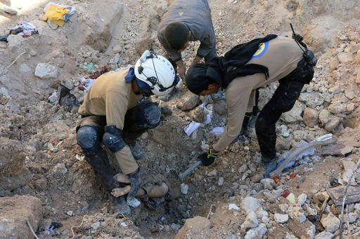 In this photo provided by the Syrian Civil Defense group known as the White Helmets, shows members of Civil Defense removing a dead body from under the rubble after airstrikes hit in Aleppo, Syria, Saturday, Sept. 24, 2016. Syrian government forces captur