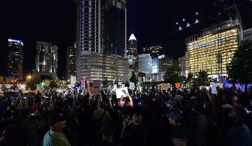 Protesters stand in unity in Romare Bearden Park as they prepare to march throughout the city of Charlotte, N.C., Friday, Sept. 23, 2016. Dozens of demonstrators are out in Charlotte for a fourth night of protests after the shooting of a black man by a po