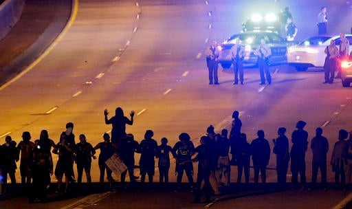 In this Thursday, Sept. 22, 2016 file photo, protesters block I-277 during a third night of unrest following Tuesday's police fatal shooting of Keith Lamont Scott in Charlotte, N.C. Protesters who have filled the streets to push for the release of video o