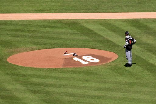 Miami Marlins player Dee Gordon stands in front of a memorial on the pitcher's mound at Marlins Park for Marlins pitcher Jose Fernanedez, Sunday, Sept. 25, 2016, in Miami. Fernandez, the ace right-hander for the Miami Marlins who escaped Cuba to become on