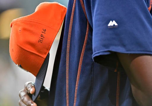 """Houston Astros relief pitcher David Paulino holds his cap with """"RIP 16"""" written on it in honor of Miami Marlins' Jose Fernandez, who was killed in a boating accident early Sunday morning in Miami Beach, before a baseball game against the Los Angeles Angel"""