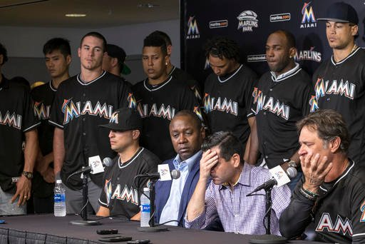 David P. Samson, center, president of the Miami Marlins, covers his face during press conference to announce the death of Marlins pitcher Jose Fernandez. Fernandez, the ace right-hander for the Miami Marlins who escaped Cuba to become one of baseball's br