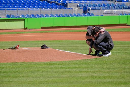 Miami Marlins player Christian Yelich, right, and teammate Justin Bour react in front of a memorial on the pitcher's mound at Marlins Park for Marlins pitcher Jose Fernanedez, Sunday, Sept. 25, 2016 in Miami. Fernandez, the ace right-hander for the Miami