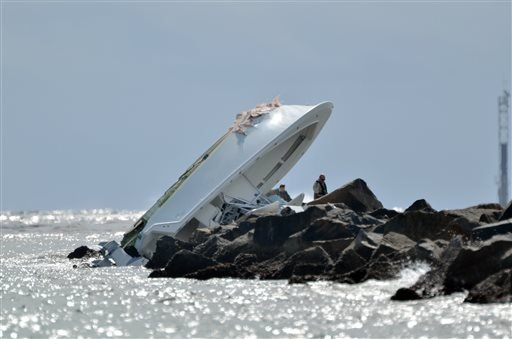 Investigators look at a boat overturned on a jetty, Sunday, Sept. 25, 2016, off Miami Beach, Fla. Authorities said that Miami Marlins starting pitcher Jose Fernandez was one of three people killed in the boat crash early Sunday morning. Fernandez was 24.
