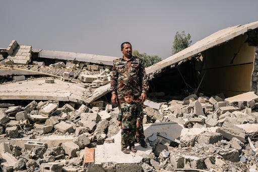 In this Aug. 9, 2016 photo, Sheikh Nazhan Sakhar, the leader of a Sunni tribal armed group, stands with his three-year-old son on the debris of his home in Hajj Ali, Iraq. He claims Islamic State militants destroyed the house, where he was born and raised