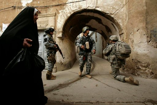 In this Thursday, April 23, 2009 file photo, an Iraqi woman passes U.S. troops and Iraqi police officers as they stand guard in the Bab al-Jadeed area of Mosul, 360 kilometers (225 miles) northwest of Baghdad, Iraq during a joint push through the west sid