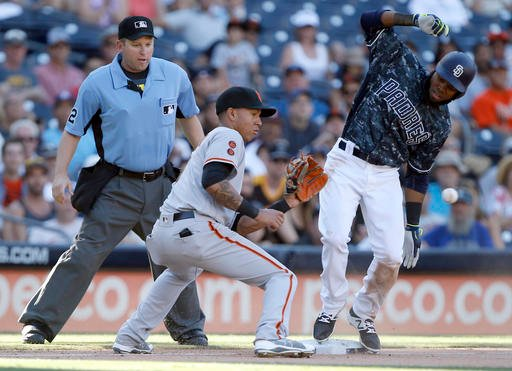 San Francisco Giants shortstop Ehire Adrianza, center, catches the ball as San Diego Padres' Manuel Margot hits a triple, with home plate umpire Clint Fagan, left, ready to make the call, during the seventh inning of a baseball game in San Diego, Sunday,
