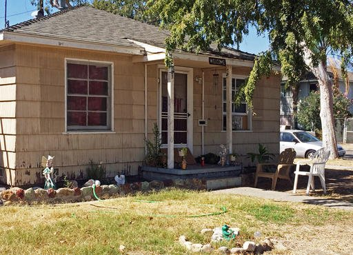 The home where three adults were found dead Saturday, Sept. 24, 2016, after a young child called 911 to report her parents had died is seen in Fullerton, Calif., Sunday. The child placed the call about 8:20 a.m. and officers were dispatched to the home, w