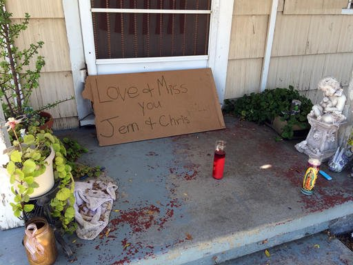 A condolence note and votive candles are seen on the front porch of the home where three adults were found dead Saturday, Sept. 24, 2016, after a young child called 911 to report her parents had died, seen in Fullerton, Calif., Sunday The child placed the