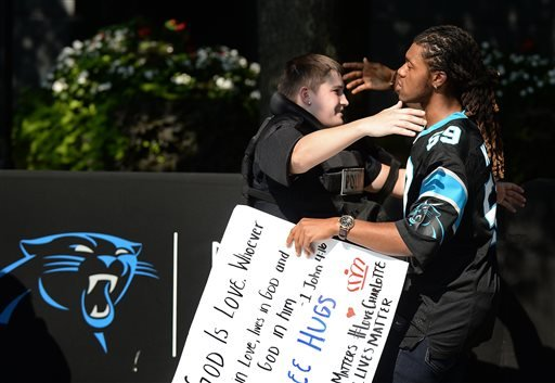 JaGerran Knight, right, reaches out to hug a Charlotte-Mecklenburg police officer at Bank of America Stadium, where people were protesting, in Charlotte, N.C. Sept. 25, 2016. (Diedra Laird/The Charlotte Observer via AP)
