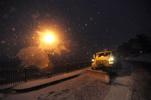 A snow plow clears snow near Lake Montebello in Baltimore Friday, Feb. 5, 2010. (AP Photo/Steve Ruark)