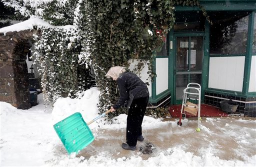 Arline Marino leaves her walker to shovel the sidewalk in front of Marino's Lunch in Staunton, VA., 2/5/10. The National Weather Service is forcasting total snowfall of 18-28 inches in the Shenandoah Valley. (AP Photo/The News Leader, Pat Jarrett)