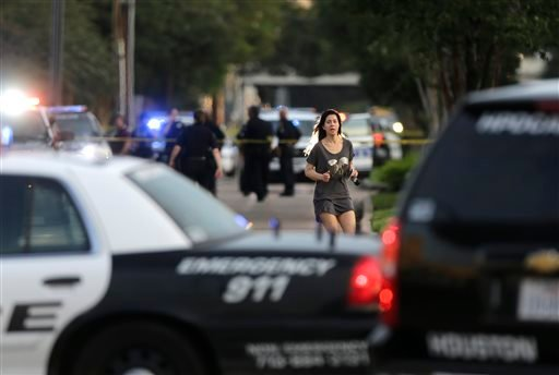 Jennifer Molleda runs down Wesleyan Street in Houston to find her husband, Alan Wakim, who had two bullets whiz by his face after going through his windshield on the way to work along Wesleyan at Law St. (Mark Mulligan/Houston Chronicle via AP)