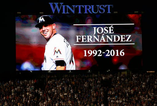 Baseball fans stand for a minute of silence for Miami Marlins pitcher Jose Fernandez, who was killed early Sunday, Sept. 25, 2016 in a boating accident in Miami, before a baseball game between the St. Louis Cardinals and the Chicago Cubs on Sunday.