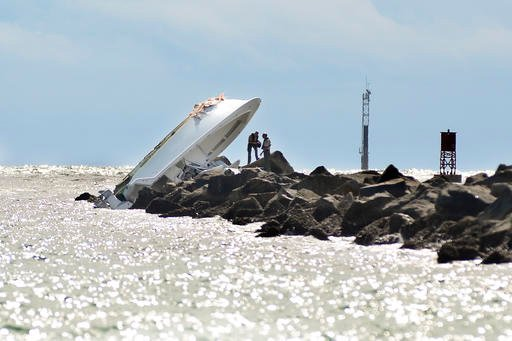 Investigators inspect an overturned boat as it rests on a jetty after a crash, Sunday, Sept. 25, 2016, off Miami Beach, Fla.