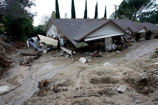 A house is covered by mud and debris after a mudslide in La Canada Flintridge, Calif., on Saturday, Feb. 6, 2010. (AP Photo/Hector Mata)