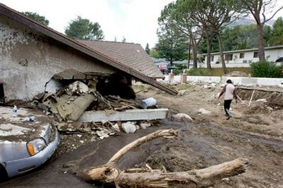 Henry Laguna walks around his property after a mudslide caused by heavy rains damaged his house in La Canada Flintridge, Calif.