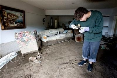Unable to stand upright due to large amounts soil covering the floor, Brian Laguna recovers personal belongings after a mudslide caused by heavy rains damaged his house in La Canada Flintridge, Calif. on Monday,