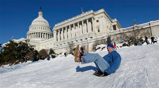 Kevin McMahon of Washington, uses an oven pan as he slides on the slope of the West Front of the U.S. Capitol, Monday, Feb. 8, 2010, in Washington. (AP Photo/Manuel Balce Ceneta)