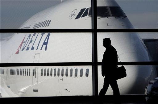 In this photo made Thursday, Jan. 21, 2010, a passenger walks past a Delta Airlines 747 aircraft in McNamara Terminal at Detroit Metropolitan Wayne County Airport in Romulus, Mich.  (AP Photo/Paul Sancya)