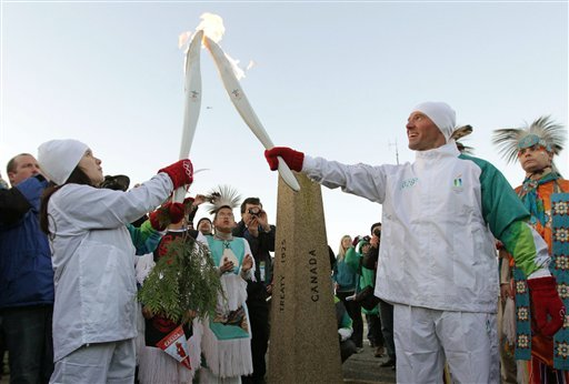 Torchbearer Rayne Williams, left, passes the Olympic flame to Phil Mahre, of Yakima, Wash., an Olympic gold and silver medalist in alpine skiing, at the Peace Arch border crossing separating Canada and the United States.