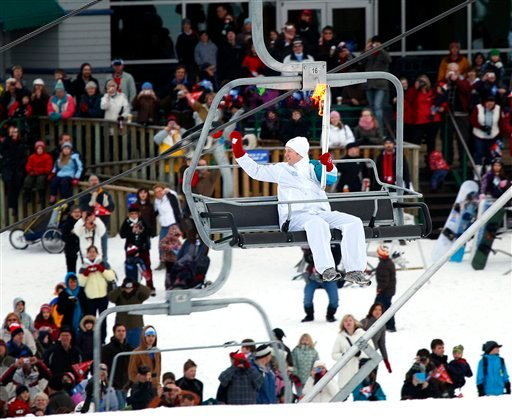 Torchbearer Stewart McDonough carries the Vancouver 2010 Olympic flame up a chairlift at Canada Olympic Park, site of the bobsled, luge, and ski jumping events at the 1988 Calgary Olympics, in Calgary, Alberta on Wednesday, Jan. 20, 2010.