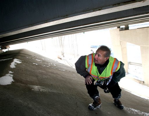 Kaz Mohan, a civil engineer with the Illinois Department of Transportation, inspects a bridge on US Route 20 in Elgin, Ill., following a small earthquake that rattled the area Wednesday, Feb. 10, 2010. (AP Photo/Corey Minkanic)