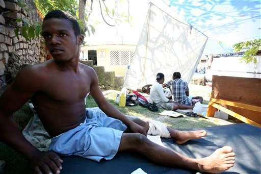 Quake survivor Benito Revolus, 23, who spent five days trapped under the rubble before being saved by an American rescue team, sits on the lawn of the Medecins Sans Frontieres aid group in Port-au-Prince, Haiti, on 1/20/10.(AP Photo/Alfred de Montesquiou)