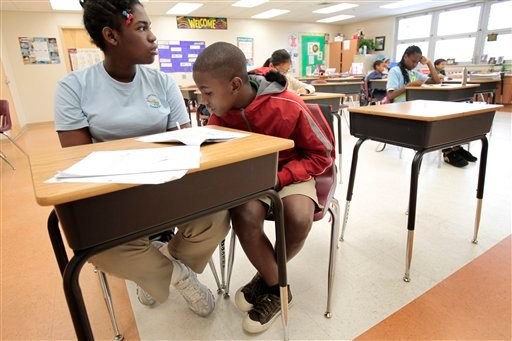 In a Thursday Feb. 4, 2010 photo, Garvey Fils-Aime, right, sits with a student tutor during class at Silver Shores Elementary School in Miramar, Fla.