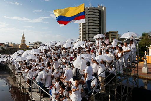 People wait for the start of the peace ceremony prior the signing of a peace agreement between Colombia's government and the Revolutionary Armed Forces of Colombia, FARC, in Cartagena, Colombia, Monday, Sept. 26, 2016. Colombia's government and the FARC w