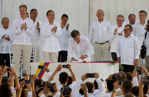 Colombia's President Juan Manuel Santos signs the peace agreement between Colombia's government and the FARC, to end over 50 years of conflict, in Cartagena, Colombia, Monday, Sept. 26, 2016. At right stands the top commander of the Revolutionary Armed Fo