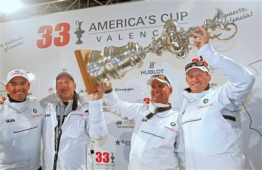 From left, BMW Oracle Racing CEO Russell Coutts, owner Larry Ellison, tactician John Kostecki and helmsman's James Spithill raise their trophy after winning the 33rd America's Cup against Alinghi in Valencia, Spain. (AP Photo/Alberto Saiz)